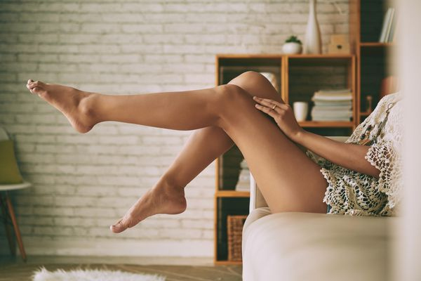 Woman sitting on couch with her bare legs kicked up