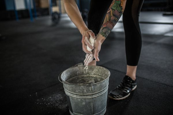 Woman applies chalk to her hands from a bucket