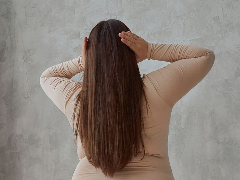Woman grabbing her long, straight hair from behind