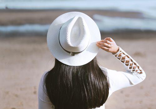 woman with shiny dark hair sitting on beach