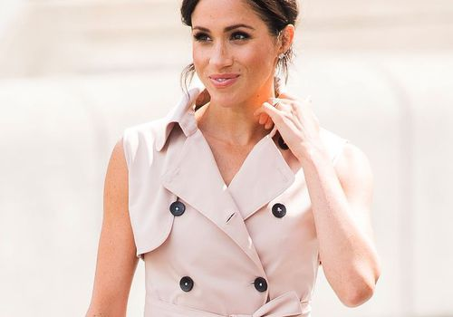 Meghan Markle with hair in low bun wearing trench dress