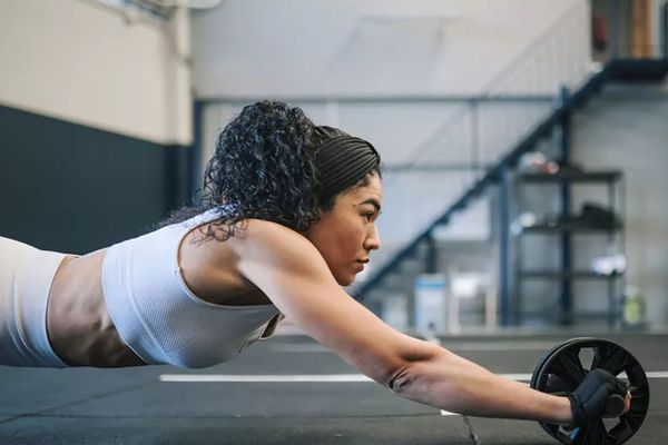 Woman in white sports set using ab roller