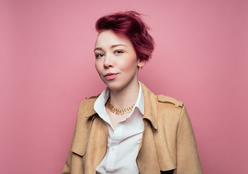 Person with short hair against a pink background