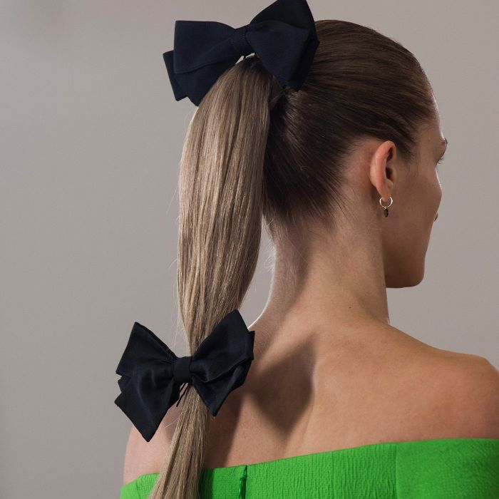 Model wearing her hair in a ponytail secured with two black bows