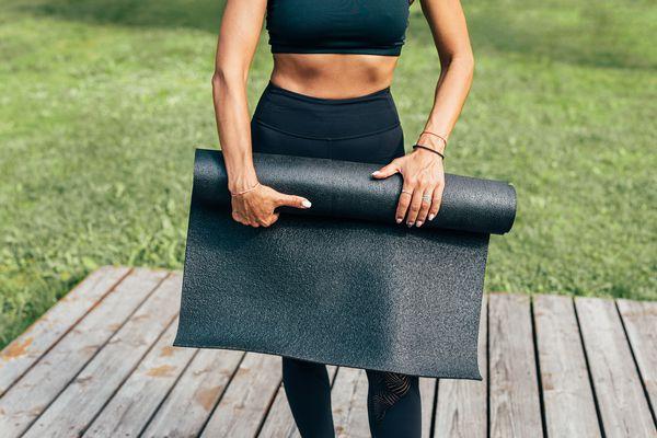 woman folding yoga mat