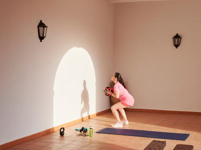 Woman performs wall ball exercises in the afternoon