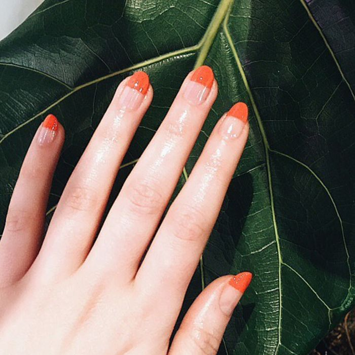 Hand with orange manicure against leaf