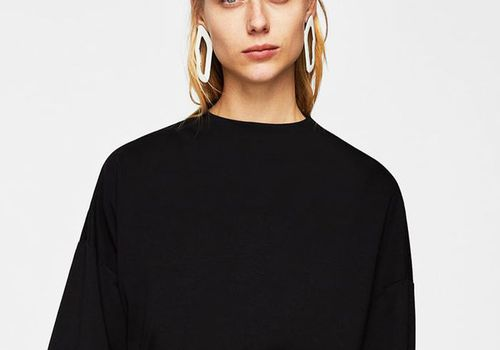 Blonde-haired woman wearing statement earrings and a black top