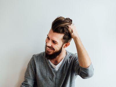 man combing hands through hair