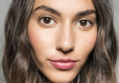 model with wavy brown hair and pink lipstick