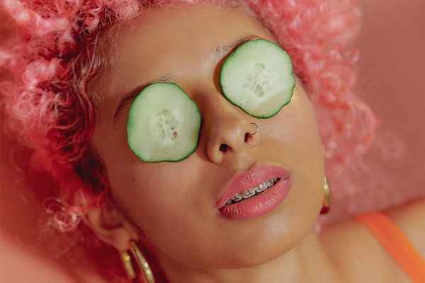young woman with pink hair with cucumber over eyes