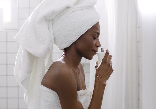 Black woman smelling perfume in bathroom