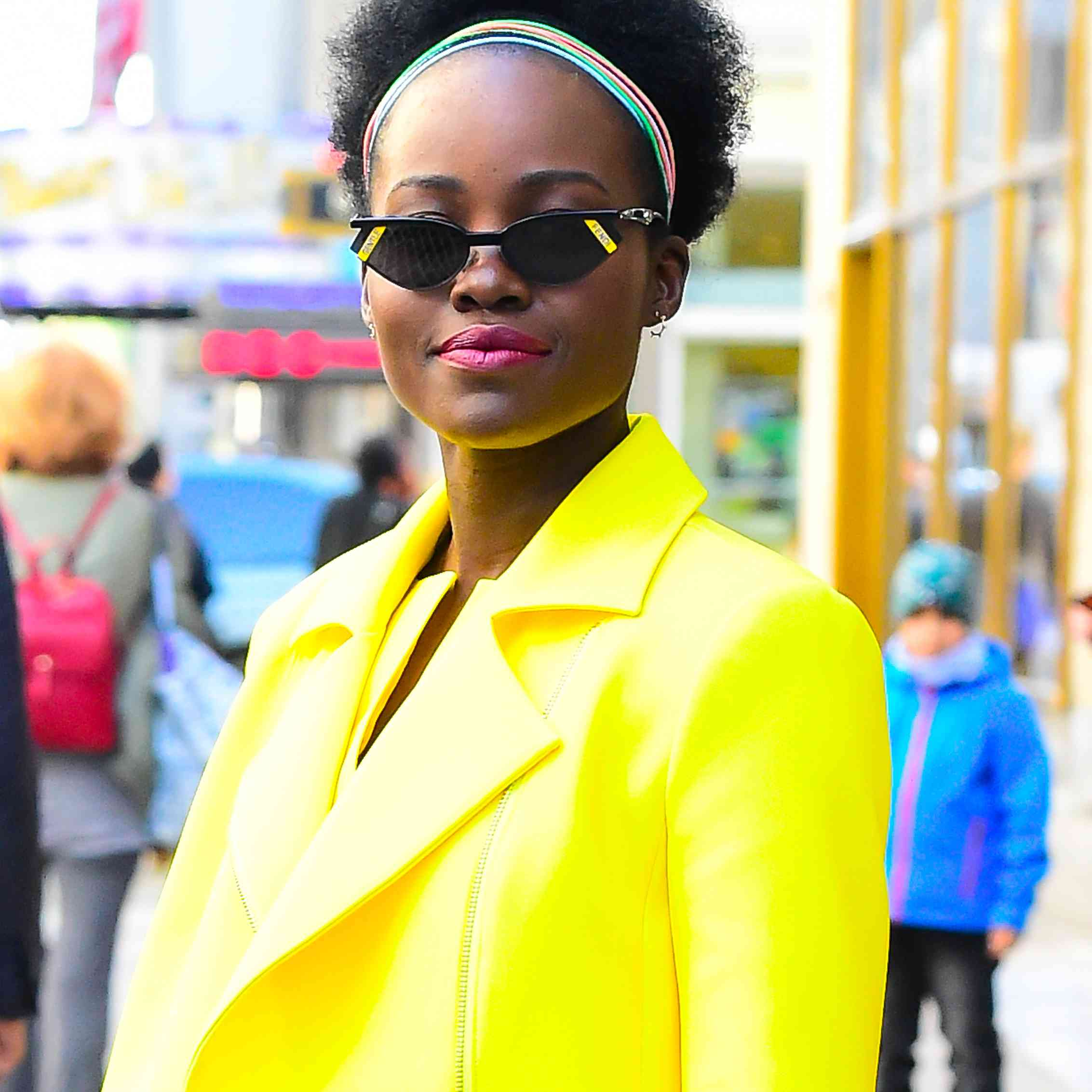 Lupita Nyong'o in Midtown New York wearing a yellow suit and magenta lipstick