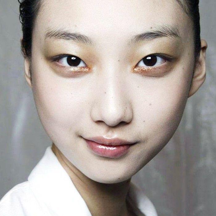 Woman wearing glittery peach eye shadow in the inner corners of her eyes
