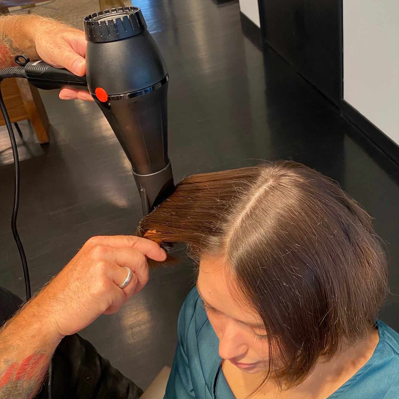 Hairstylist using a blowdryer to create a center part in a client's hair