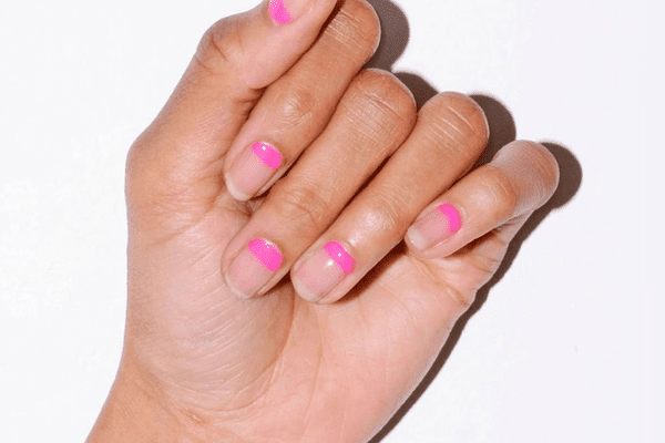 woman with pink minimal manicure against white background