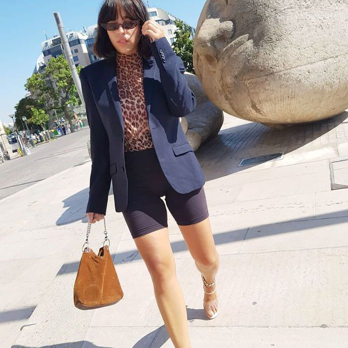 Young woman styles a turtleneck with a blazer and biker shorts and sandals