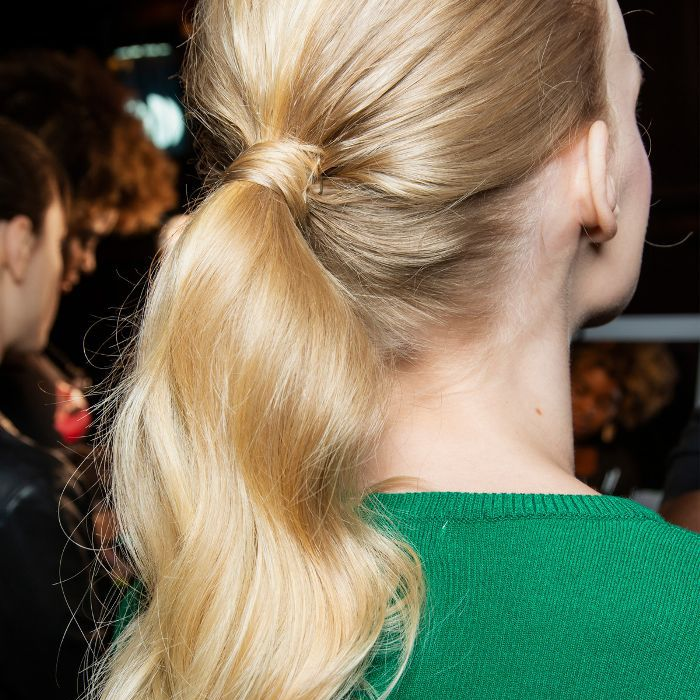Model wearing her hair in a sleek, wavy ponytail