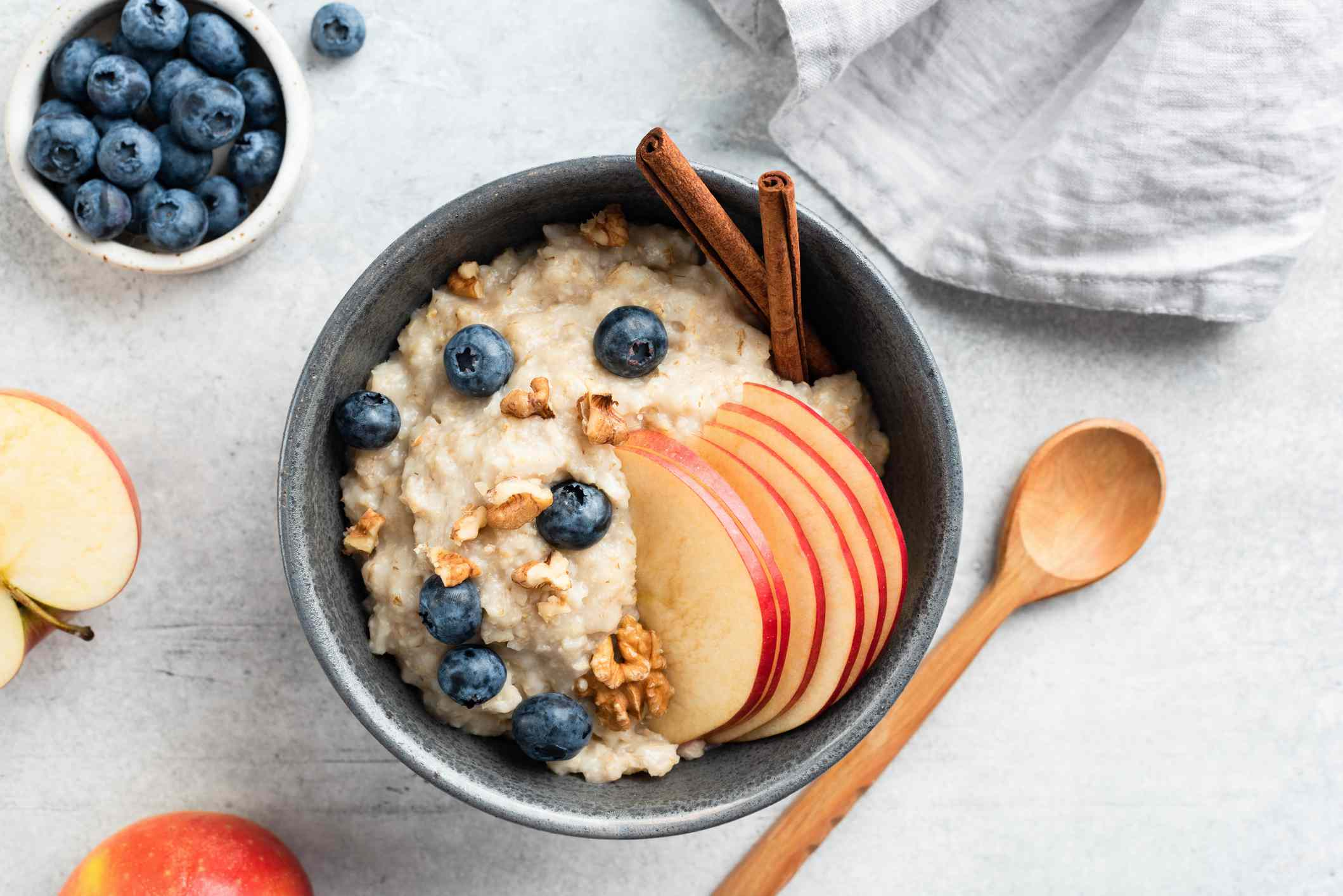 A bowl of oatmeal topped with apple, blueberries and nuts. Sitting on a counter beside a spoon, dish towel and fruit.