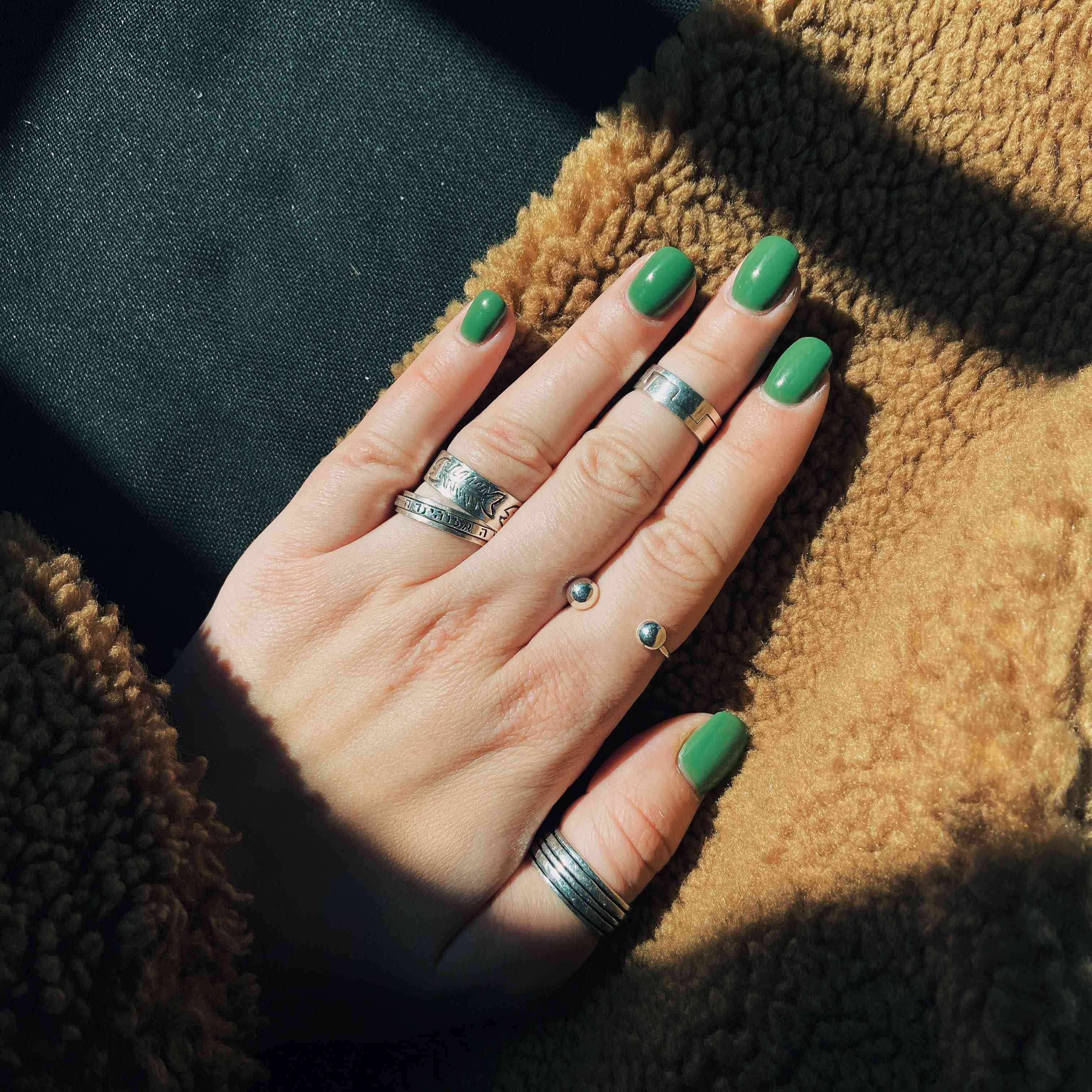 green manicure against furry fabric with silver rings