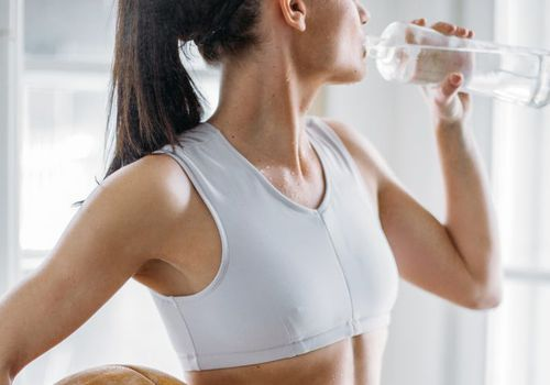 woman with ball drinking water in sports bra