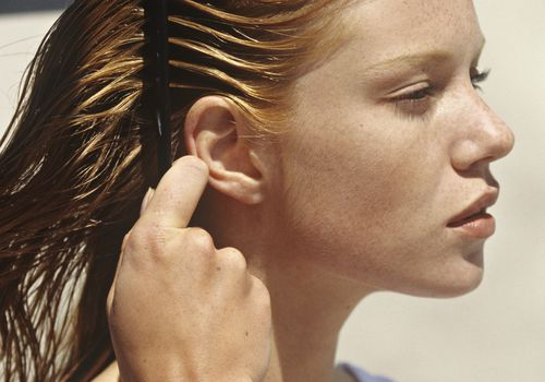 Freckled woman combing her hair