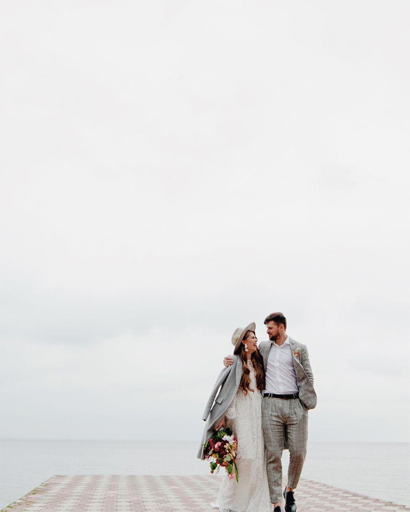 couple walking down pier on wedding day