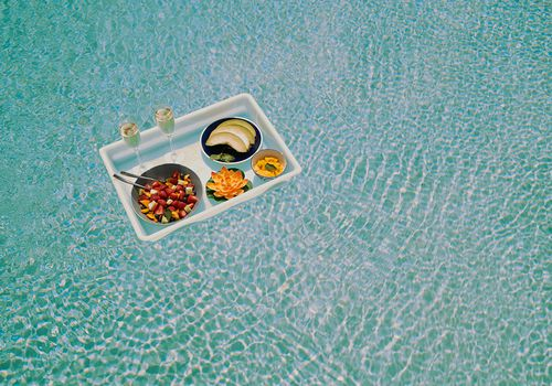tray of fruit and champagne floating in pool