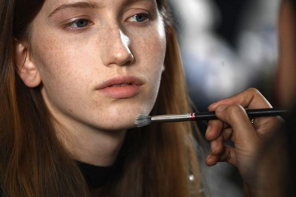 Model having makeup applied backstage at fashion show