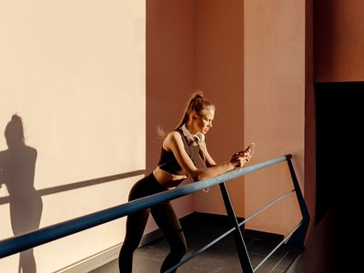 Woman in workout gear standing on a balcony, looking at her phone