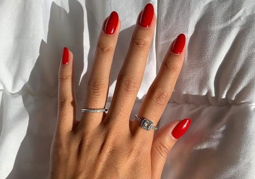woman with red nails and two rings