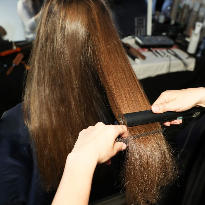 Model having her hair straightened with a flat iron backstage