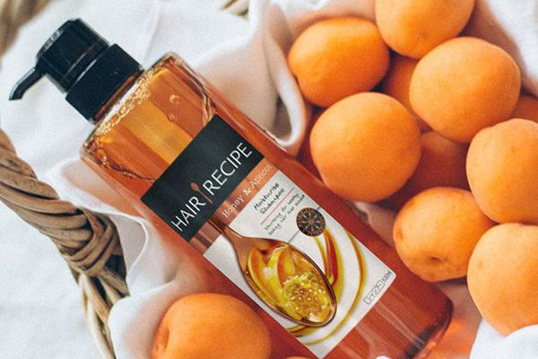 Hair Recipe Honey & Almond Shampoo lying in woven basket with apricots