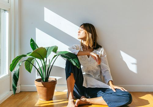 woman staring out window next to plant