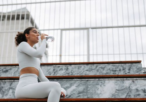 woman drinking water after workout