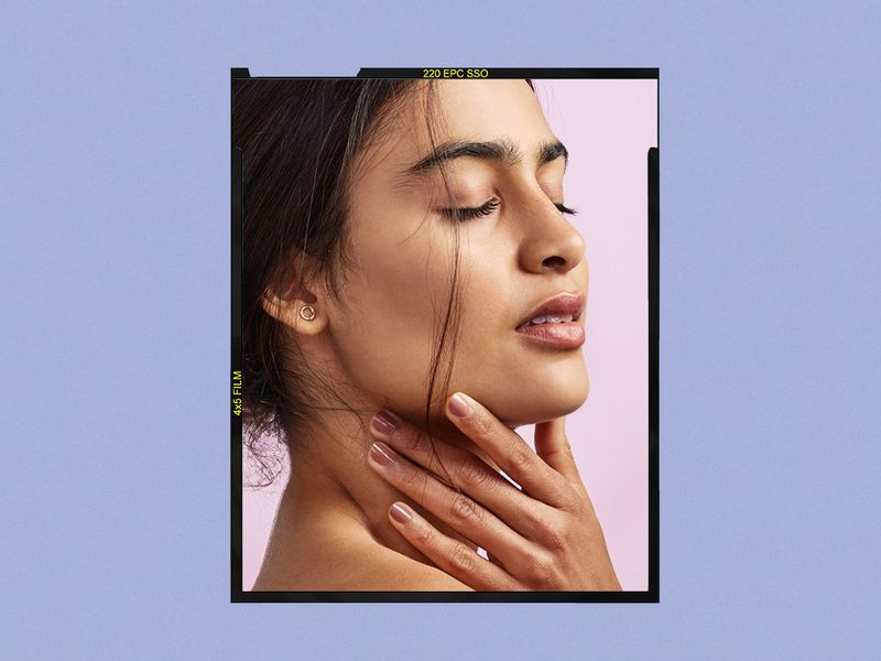 South Asian woman touches her face