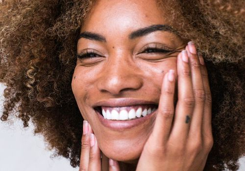 black woman touching her face smile
