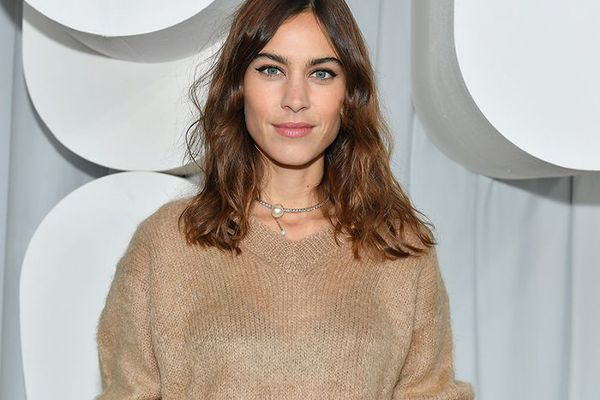 Alexa Chung with wavy, shoulder-length hair wearing beige sweater