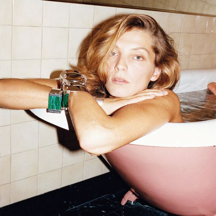 Blonde-haired woman in pink bath tub with her arms folded over the edge