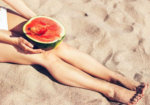 woman with bare legs holding a watermelon