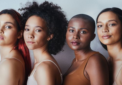 Four young women with various hair types against a grey background