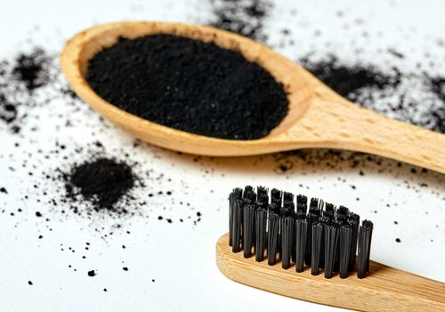 Charcoal on a wooden spoon with bamboo toothbrush
