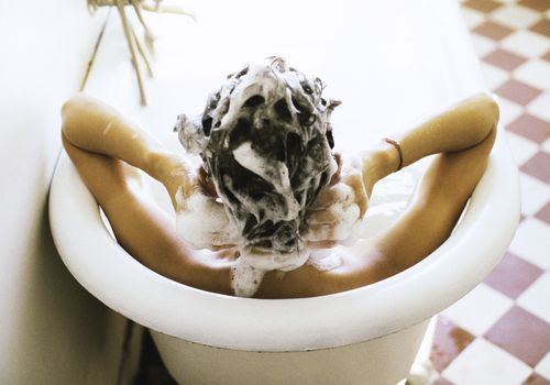 Woman in bathtub washing hair
