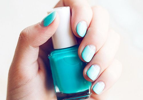 woman with blue nail polish holding bottle