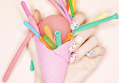 Hand with colorful manicure holding pink ice cream cone filled with colorful, deflated balloons