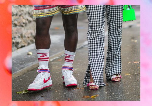 A masculine person in Nikes with a feminine person in heels