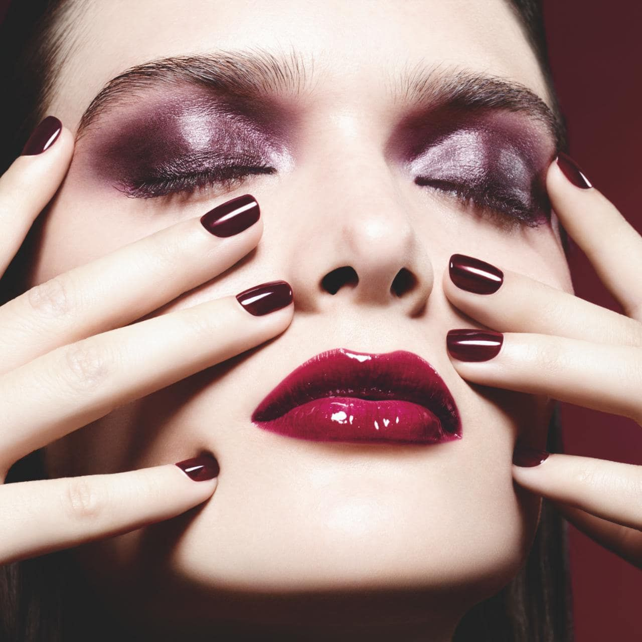 A woman wearing purple eyeshadow and Chanel Rouge Noir nail polish.