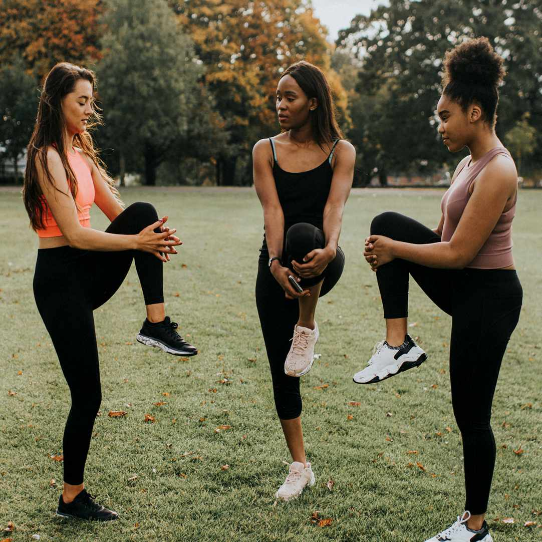 three friends working out in the park