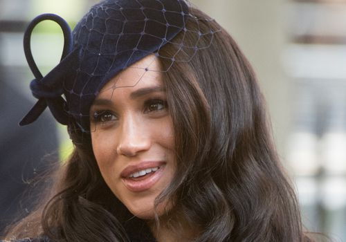 meghan markle looking to the side wearing black fascinator
