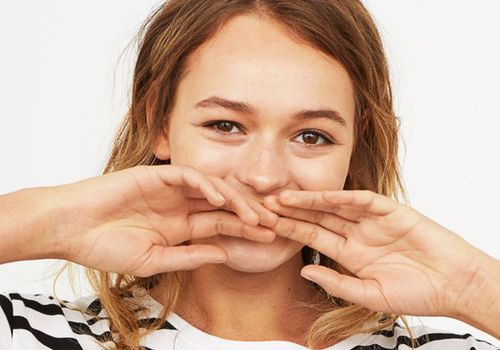 woman smiling covering her mouth